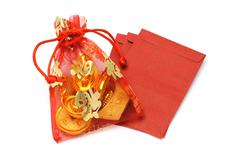 gold ingots and coins in decorative sachet and red packets - stock photo
