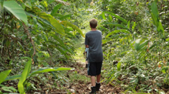 young boy swings machete on forest path - stock footage