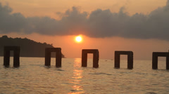 Colorful dolly shot of sunset over broken pier Stock Footage