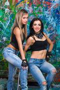 Two young girls stands near wall with graffiti Stock Photos