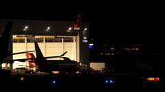 4K - Tow tractor pulling plane out of airport hangar Stock Footage