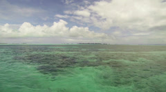 Traveling across a pale blue sea toward islands on the horizon Stock Footage
