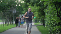 Man jogging in city park, super slow motion, shot at 480fps HD Stock Footage
