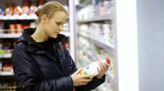 Woman putting a bottle of milk in her shopping basket Stock Footage