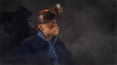 Coal miner looking at coal in cave Stock Footage