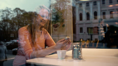 Woman with phone in cafe enjoying outside view Stock Footage