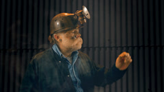 Miner looking at gold nugget Stock Footage