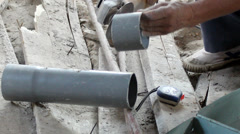 Worker cutting plastic Pipe by circular saw Stock Footage