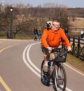 Man ride bike with cat - stock photo