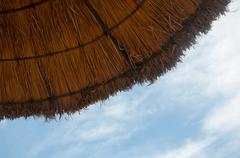 straw beach umbrella and bright sun - stock photo