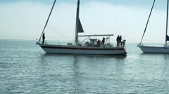 People on two sailboats greet each other. Stock Footage