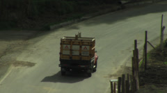 Tracking bright truck on rural road Stock Footage