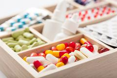 medical pills and ampules in wooden box - stock photo