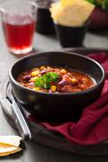 Mexican chili con carne in black bowl with tortilla Stock Photos