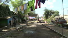 Washing hung to dry over railway track, a dog wags tail Stock Footage