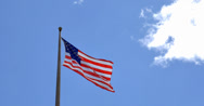 Stock Video Footage of 4K American flag - star and stripes floating over a cloudy blue sky