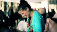 Young woman watching funny film on tablet computer at airport HD Stock Footage