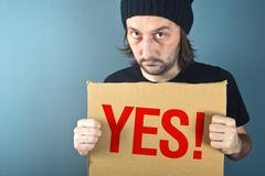 Man holding cardboard paper with word Yes Stock Photos