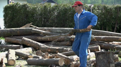 Man carry branch log away from pile Stock Footage