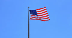 4K American flag - star and stripes floating over a blue sky - stock footage