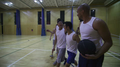 Competitive basketball team coming off court after practise - stock footage
