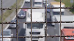 Out of focus traffic through wire fence - stock footage
