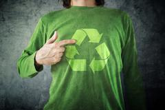 RECYCLE. Man pointing to recycling symbol printed on his shirt Stock Photos