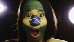 Female brazil fan is happily surprised on black background (close up) Stock Footage
