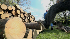 Kicking log on to pile of wood with leg in slow motion Stock Footage