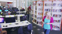 Diverse group of students working together in study area of modern university - stock footage