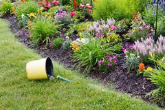 Overturned bucket containing garden tools Stock Photos