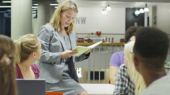 Female teacher in modern college teaching a class of students - stock footage