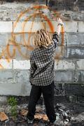 Hooligan painting graffiti on the building Stock Photos