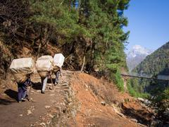Sherpa Porters Walking Uphill, Everest Base Camp Trek, Nepal - stock photo