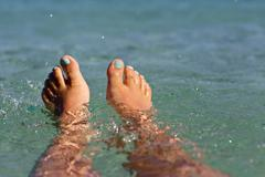 Teenagers legs in sea, Greece Stock Photos