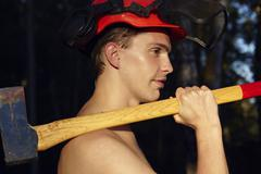 Young man with axe on shoulder - stock photo