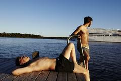 Two young men on jetty, Sweden Stock Photos