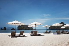 Sunchairs and sunshades on sandy beach, Malaysia Stock Photos