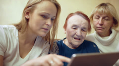 Woman with pad showing photos or video to her mother and grandmother Stock Footage