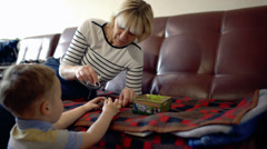 Grandmother and grandson playing with toy animals at home Stock Footage