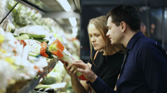 Man and woman buying fresh vegetables in grocery - stock footage