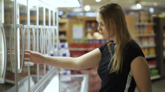Young couple. Woman taking meal from the fridge, they checking it and leaving Stock Footage