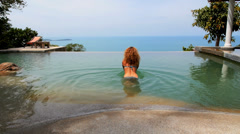 Woman Swimming and Enjoying Seascape from Endless Pool in Luxury Resort - stock footage