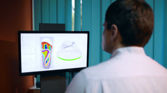 Doctor working with shoe modeling using foot scan Stock Footage