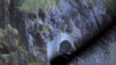 Rain on windshield, wiper and rocks in the background Stock Footage