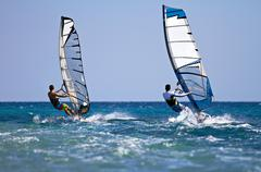 two windsurfers in action - stock photo