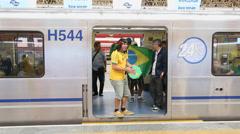 Brazilian Fan plays tambourine in subway Stock Footage