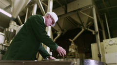 Workers in a beverage factory sorting and packing packets of fresh coffee - stock footage