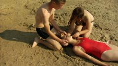Pulling an unconscious girl from the water onto the beach, starting CPR Stock Footage