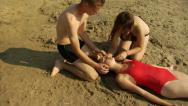 Stock Video Footage of Pulling an unconscious girl from the water onto the beach, starting CPR